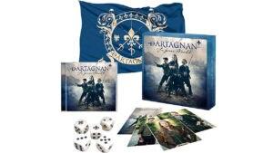 """Die Fan-Box beinhaltet eine dArtagnan-Fahne (Maße: 110 x 75), eine handsignierte Band-Fotokarte, Portrait-Fotokarten, 5 Würfel inkl. dArtagnan Lilien Logo (anstelle der """"1"""") und das Würfelspiel """"dArtagnan"""""""