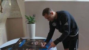 Manuel Neuer signiert das Plakat